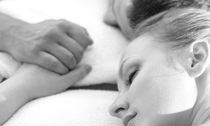 woman and man lying down to a massage holding hands